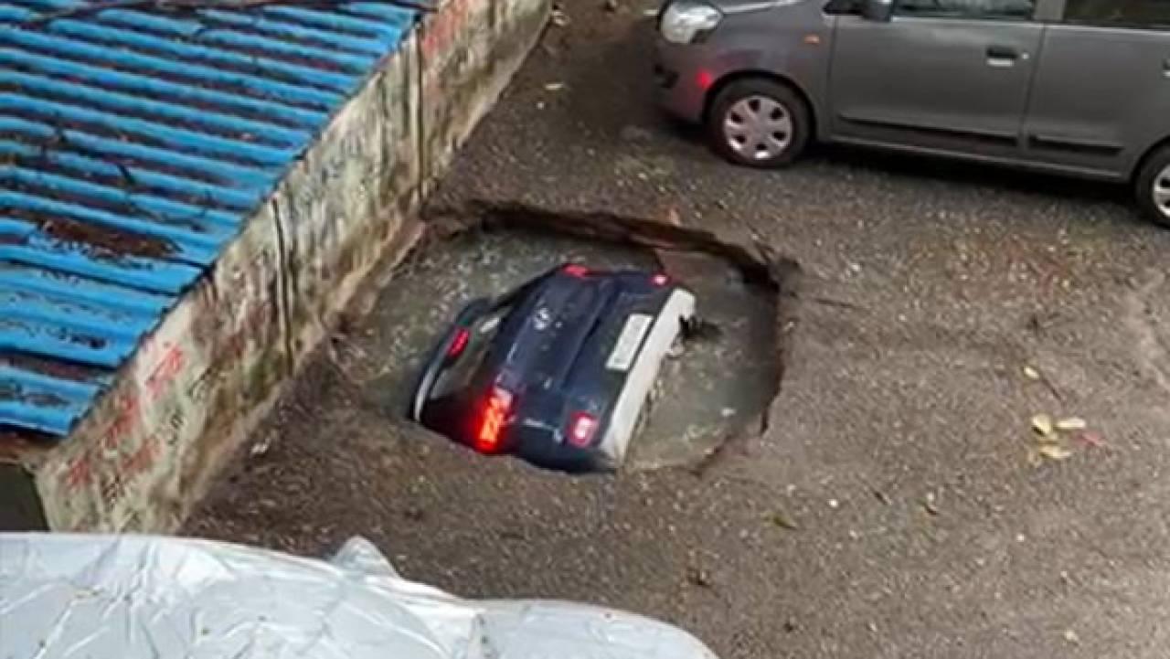 Mumbai, India. Auto inghiottita dalla strada in seguito alle piogge abbondanti