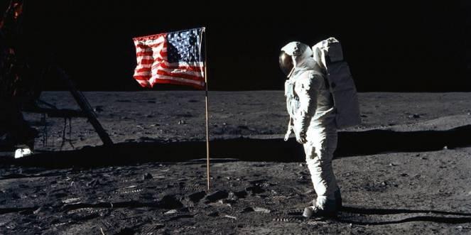Aldrin cammina vicino al modulo lunare e alla bandiera degli USA